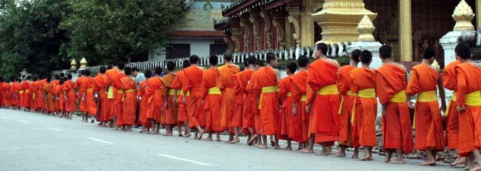 monks gathering alms outside wat sene, luang prabang